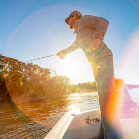 An angler casts off a boat at sunset.