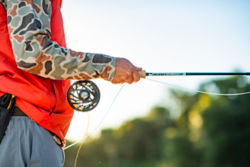 An angler wearing a camo-print long-sleeve and bright orange vest holds a Helios 3 rod with a Mirage reel.