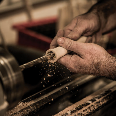 Hands working at a lathe hollowing out a fly rod grip.