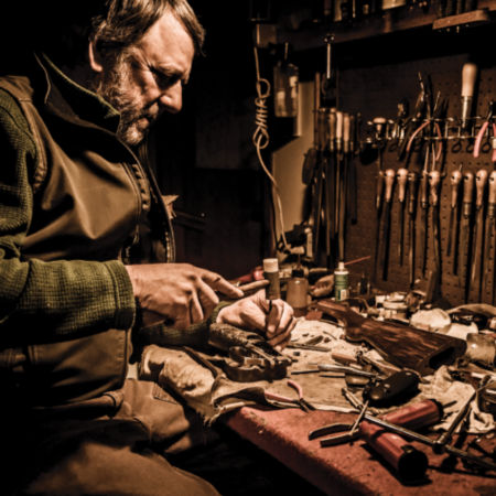 Image of a man working on reel on a workbench