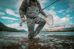 An angler wearing waders splashes through the shallow water of a mountain lake.
