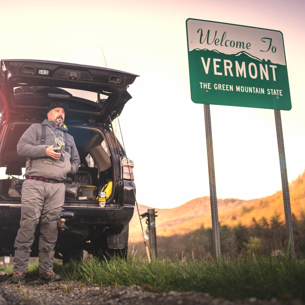 Man standing next to Vermont state sign