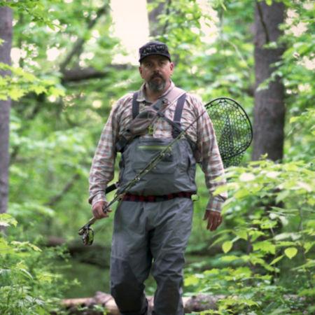 Man walking through woods in fishing waders