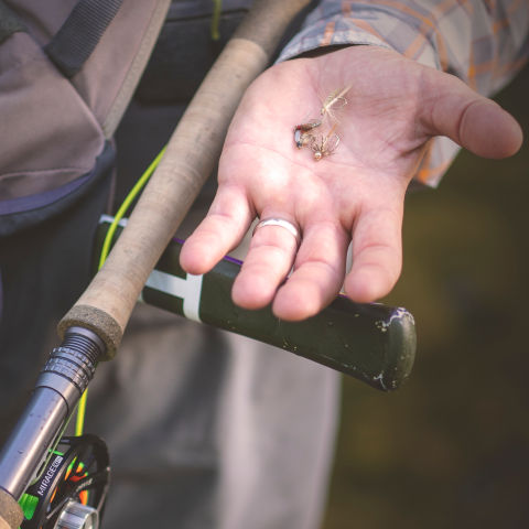 Man holding flies and a spey rod