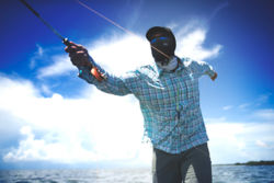 A sunglass-wearing angler with a buff pulled up over their face casts under sunny skies.