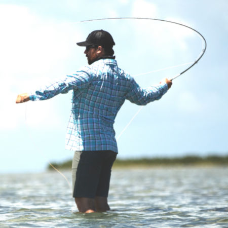 Man standing in water with a bent fly-rod.