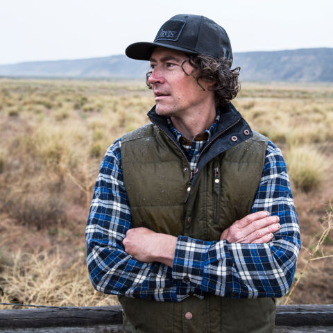 Man wearing flannel shirt and vest with arms crossed looking off to his right.