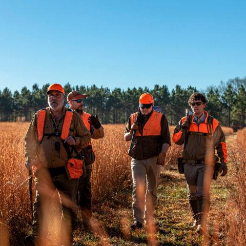 Group of hunters walking in a field