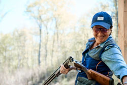 Smiling woman reloading a shotgun for clays shooting