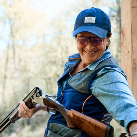 A smiling woman in a blue ball cap reloading a shotgun for clays shooting