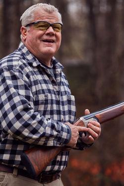 man in a plaid shirt holding a gun