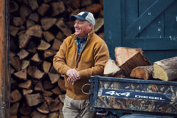 man in front of wood pile