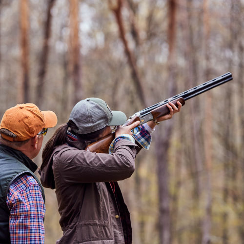 Instructor giving a woman shooting instruction