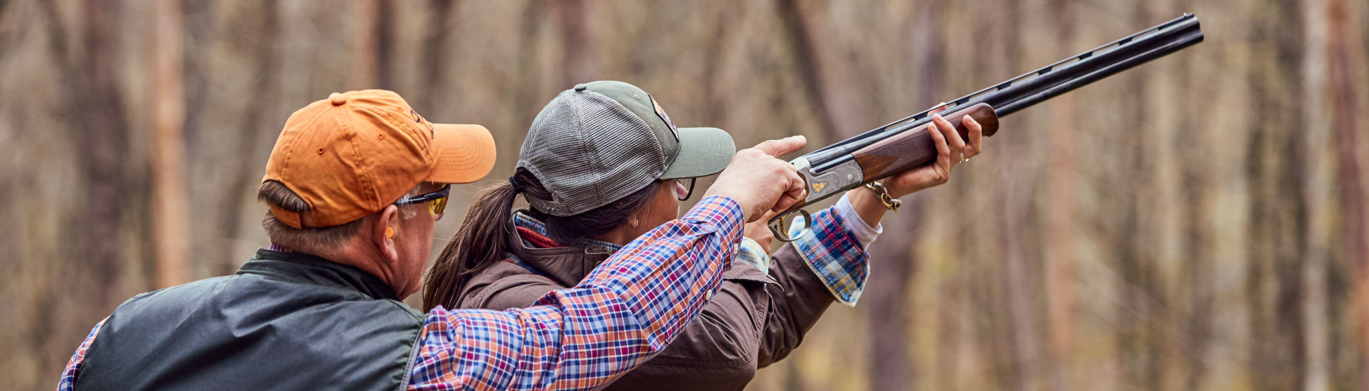 An instructor teaching a student to shoot clays