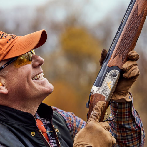 Hunter with gun, looking upward, smiling