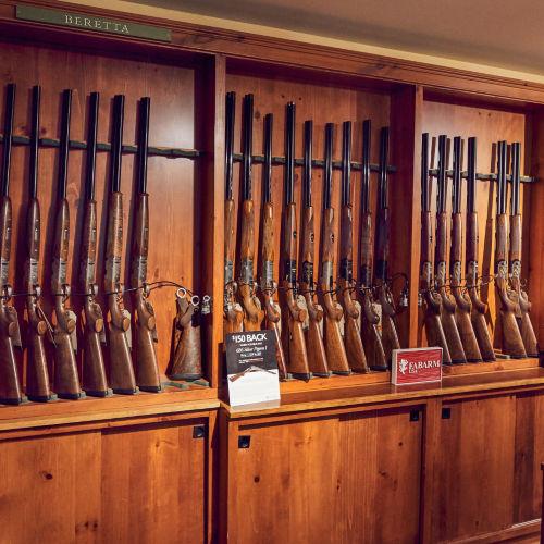 Wooden racks of shotguns line the wall of Orvis's Sandanona Shooting Grounds.