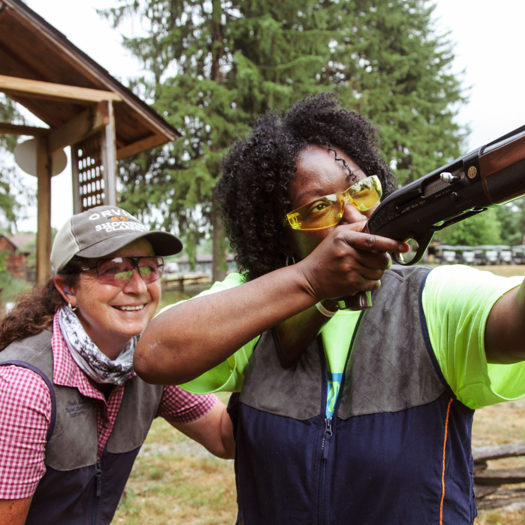 A woman being taught how to shoot