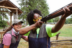 female instructor stands behind another woman shooting