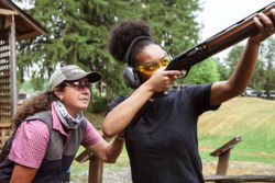 instructor standing behind shooter
