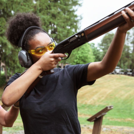 A girl takes aim with her shotgun.