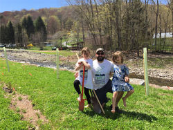 father and his two daughters standing next to a stream