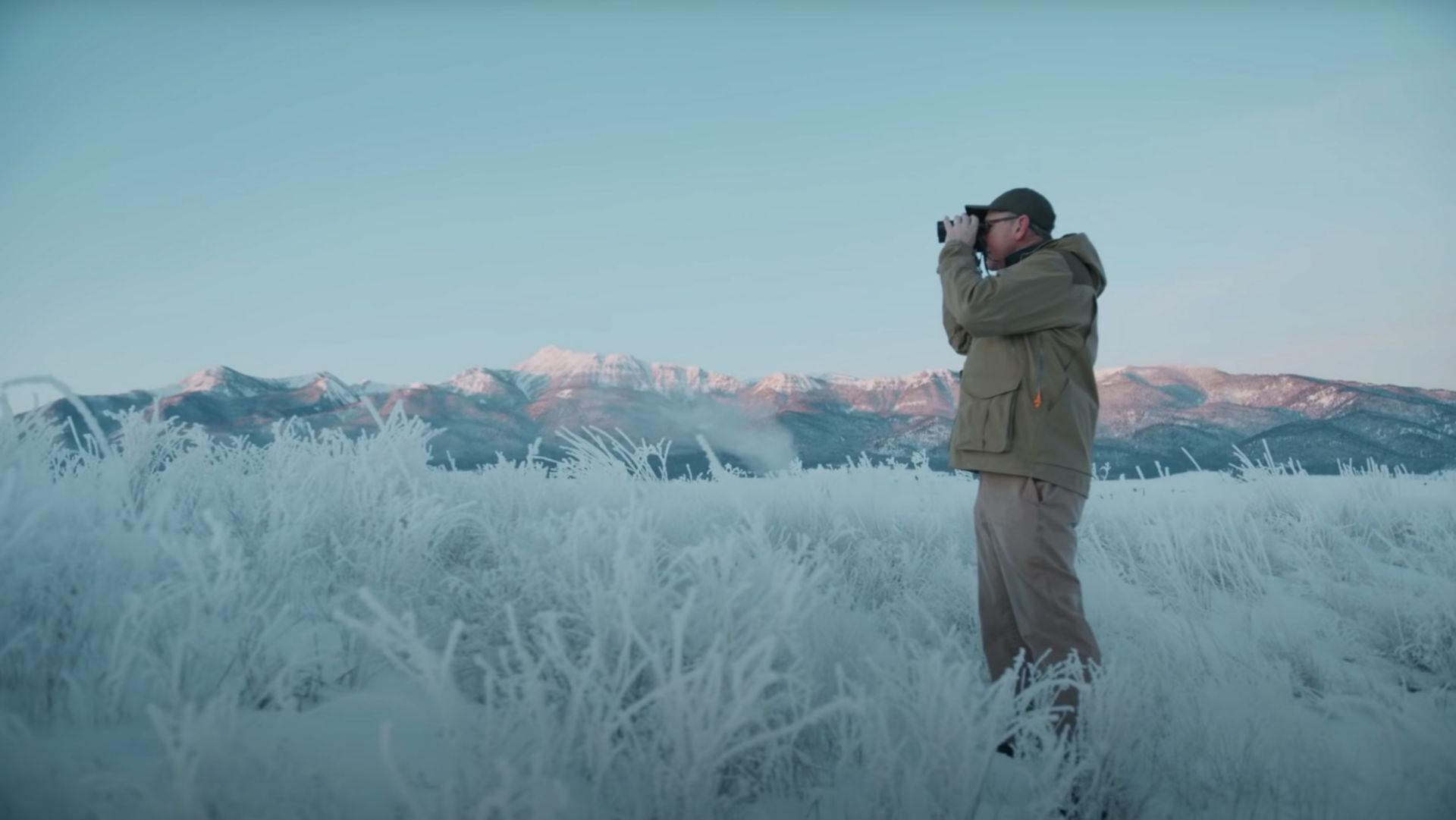 man in frozen field looking through binoculars