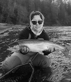 Black and white photo of Tracy Nguyen-Chung holding a fish in the water