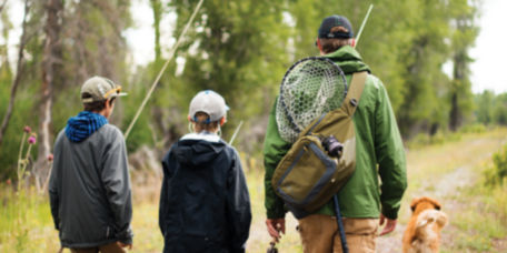 Dad walking down a path with his two boys, a dog, and fishing rods in hand
