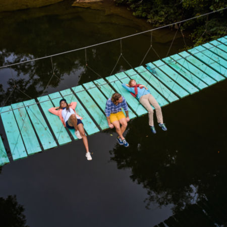 Three people laying across a blue wooden bridge in Belize