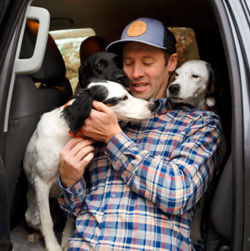 Simon Perkins cuddling with his dogs inside a vehicle.