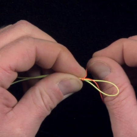 A close-up of fingers tying a knot