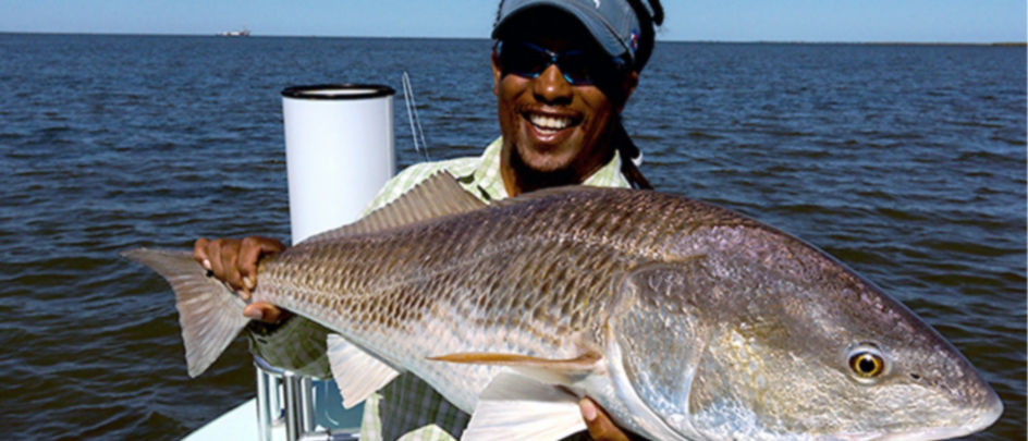 Man holding a Redfish out on the water