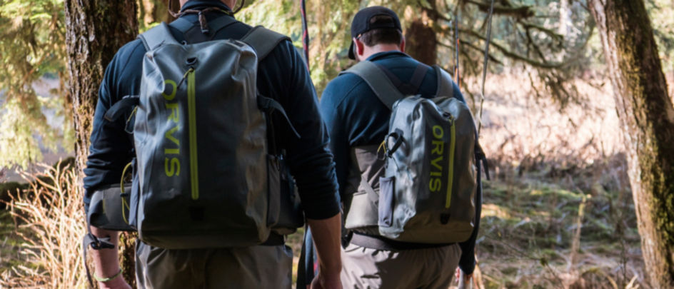 Two people walking along a river wearing Orvis packs and Orvis waders