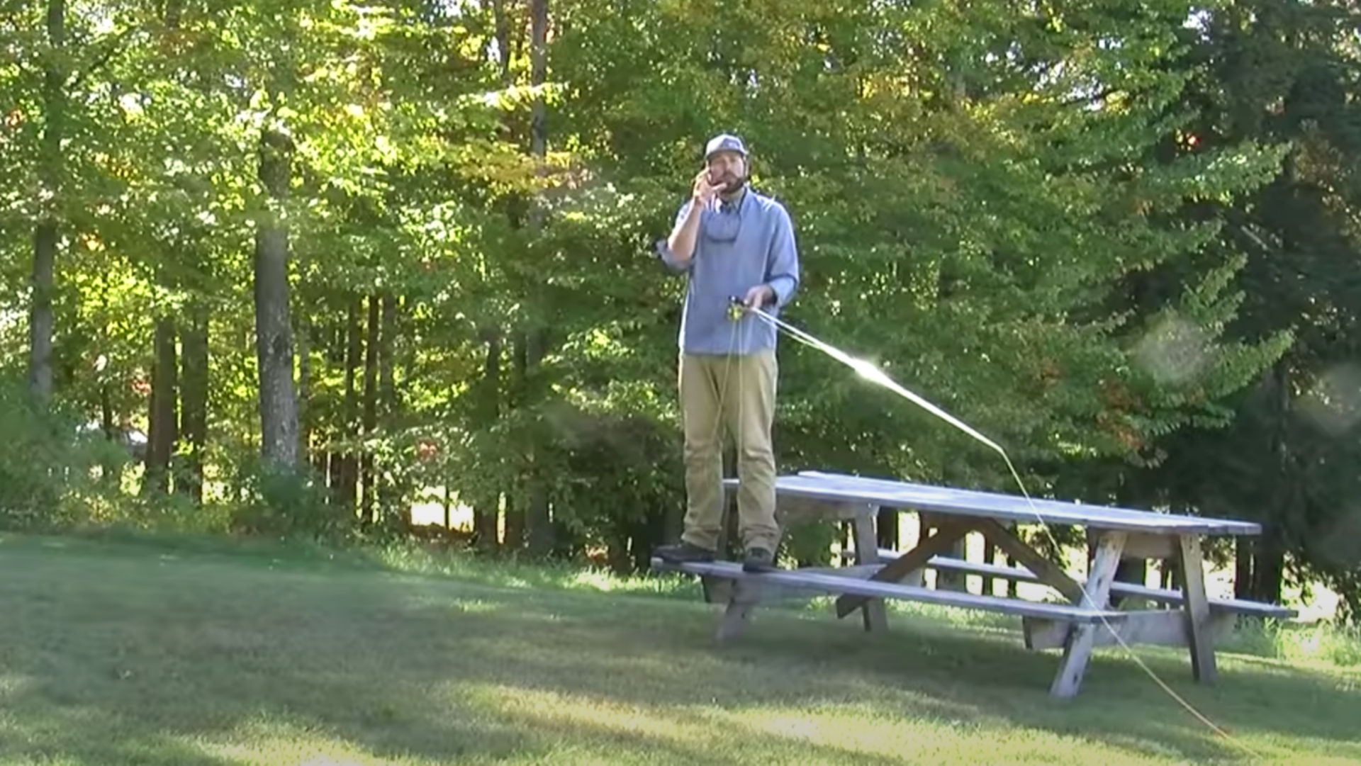 instructor holding a fishing rod while standing on a bench