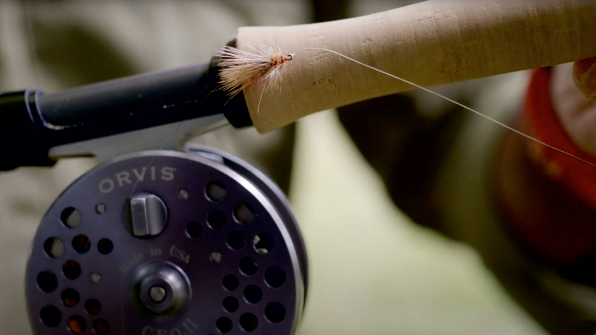 A close up image of fly rod and reel with fly