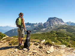 Hiker and her dog in the mountains