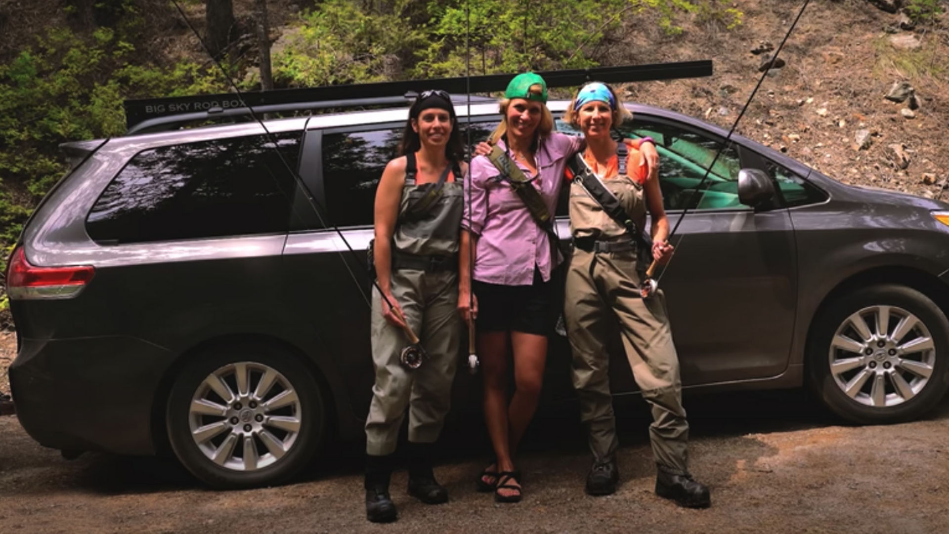 three women in fishing gear standing in front of a car