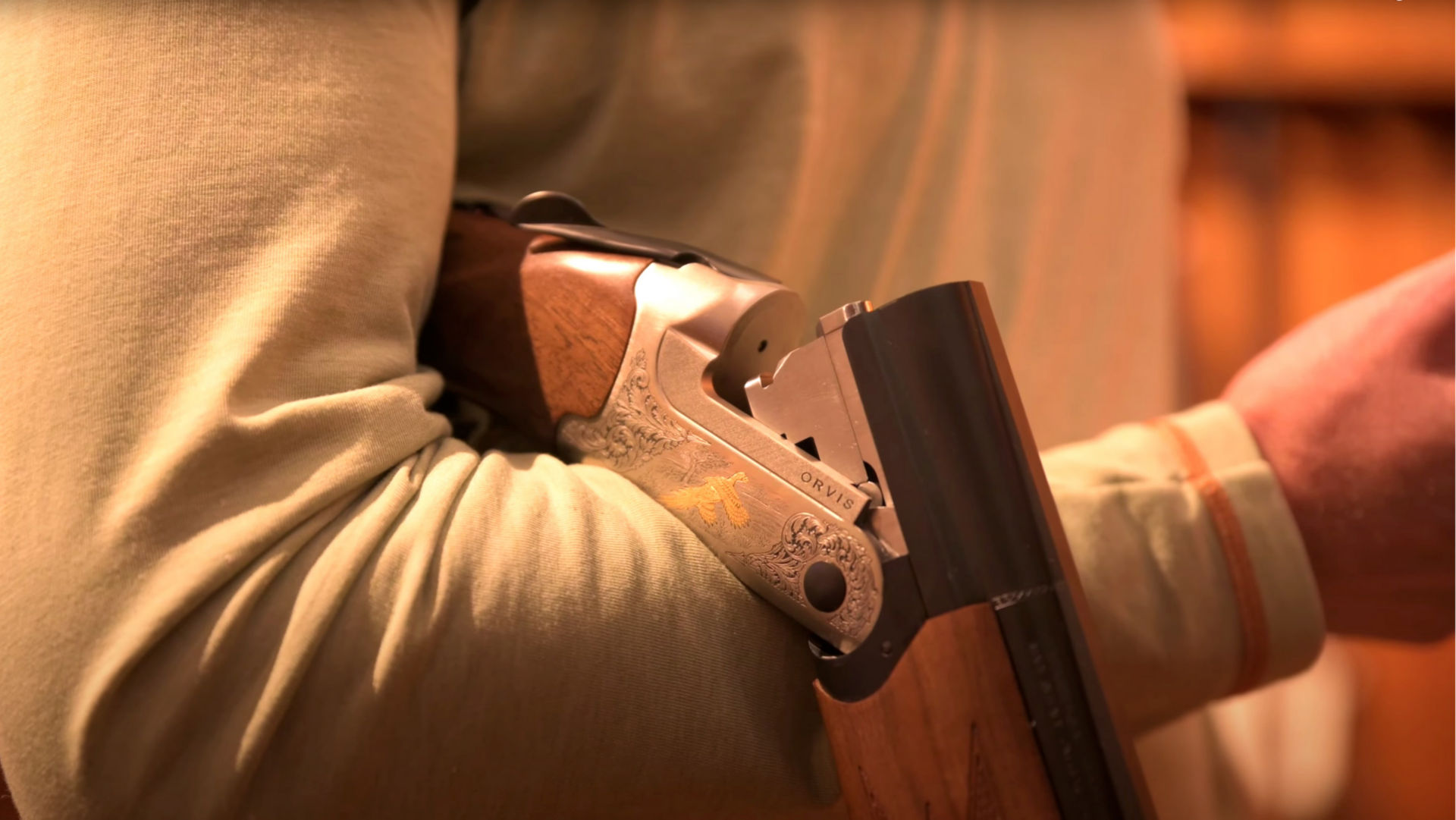 close up of a shotgun being held correctly over an arm