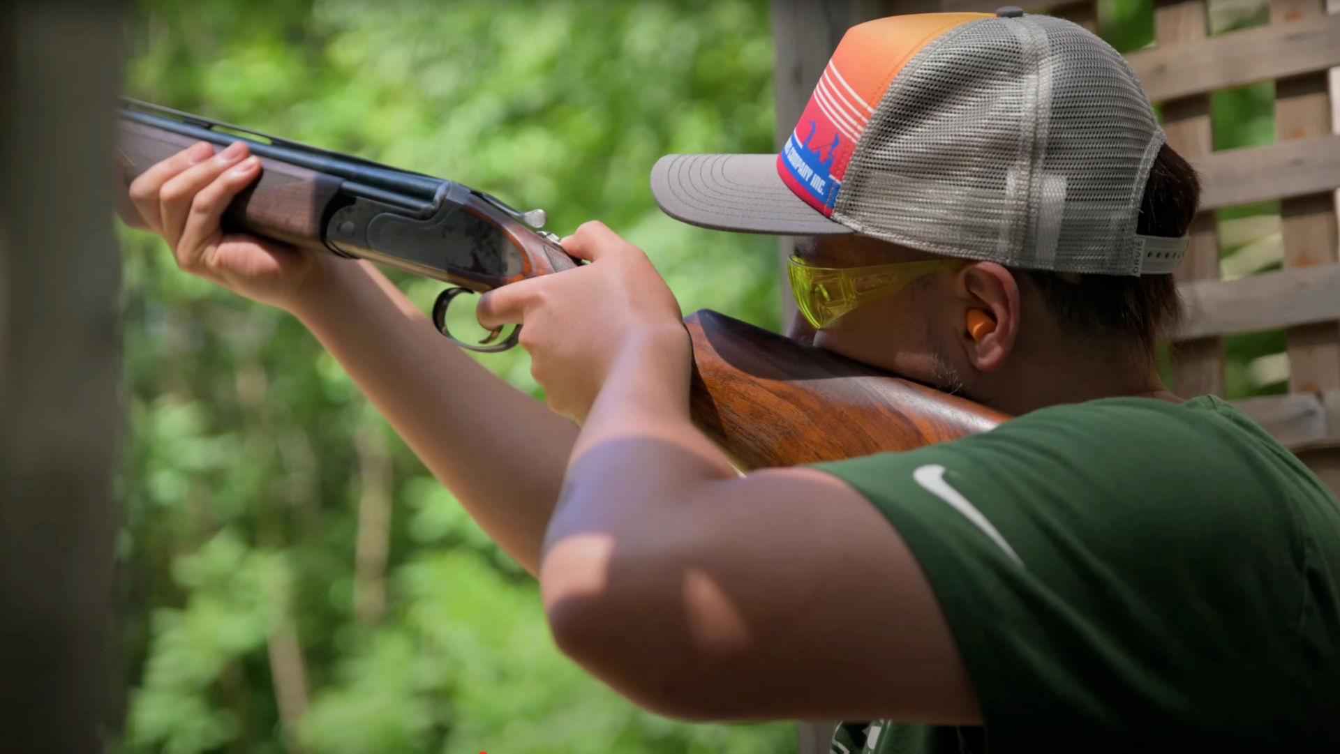A man in a ball cap sighting a shotgun at a range