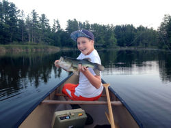 Kid holding largemouth bass in canoe