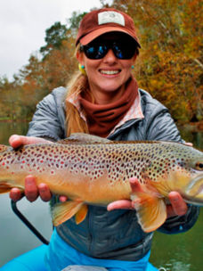 woman holding a brown trout